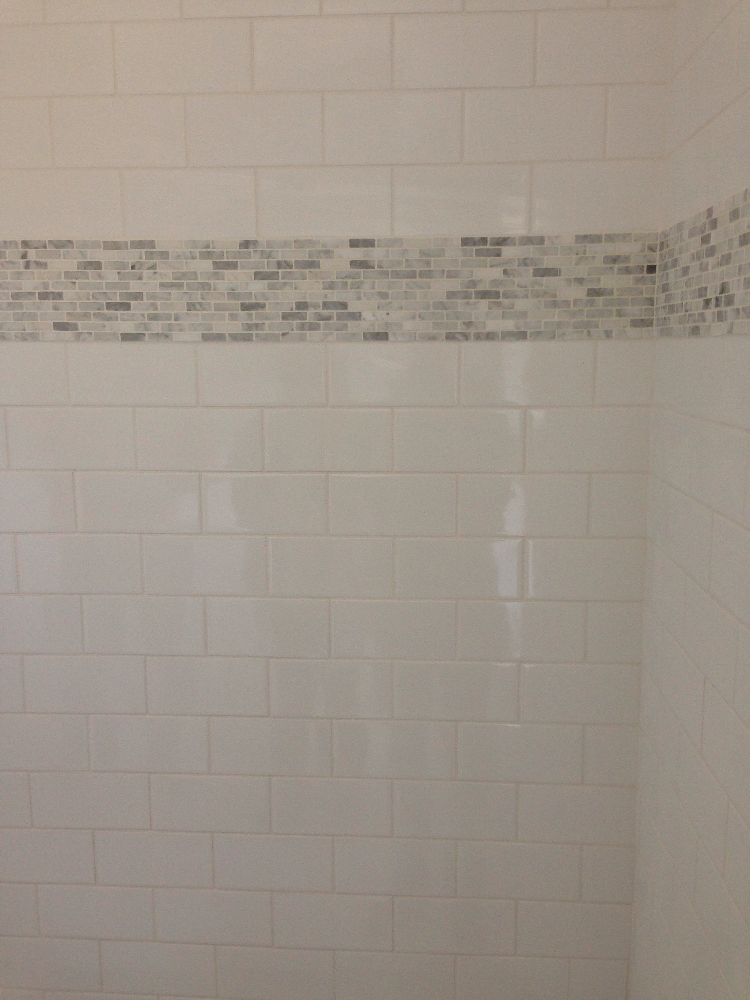 ... tile with Carrera marble rectangular accent band in the master shower